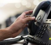 close up employee man hand touching handset of  telephone on desk for contact customer or receiving call , hotline  concept